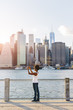 USA, New York City, Brooklyn, woman standing at the waterfront taking cell phone picture