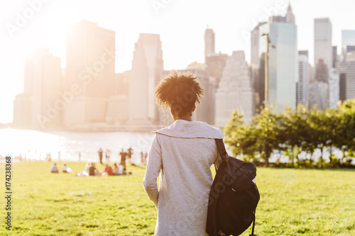 USA, New York City, Brooklyn, woman standing on meadow looking at the skyline
