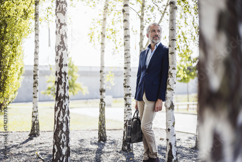 Businessman holding bag leaning against a tree