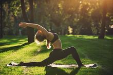 Beautiful Young Woman Practices Yoga Asana Virabhadrasana 1 - Warrior Pose 1 In The Park At Sunset