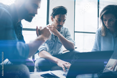 Fotografía  Group of young coworkers discussing ideas with each other in modern office