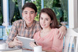 young couple using tablet in coffee shop