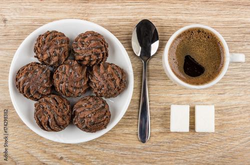 Plakat Okrągłe ciastka czekoladowe w spodku, czarnej kawie, cukrze i łyżce