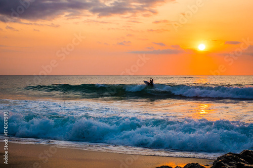 Poster Mer / Ocean French sunset surfer catching a wave