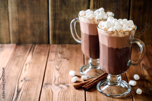 Hot chocolate with marshmallow in glass cups on wooden background