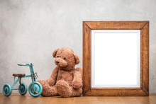 Retro Oak Wooden Photo Frame Blank And Plush Teddy Bear With Toy Tricycle On The Desk Front Old Textured Concrete Wall Background. Vintage Style Filtered Photography