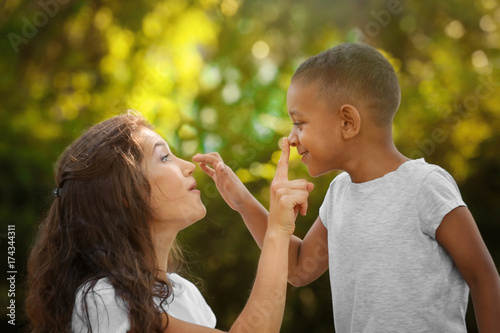 Photo Young woman with adopted African American boy outdoors
