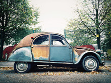 A Rusty, Multi Colored Citroen Car.
