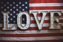 American Flag With The Word LOVE On It In Metal Illuminated Letters