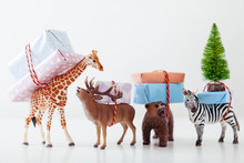 Toy Animals Carrying Christmas Gifts On White.