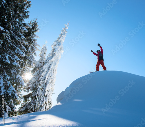 Tuinposter Wintersporten Male snowboarder freerider standing on top of the ski slope with his arms in the air in victorious gesture in the mountains copyspace recreation snowboarding extreme lifestyle sports concept