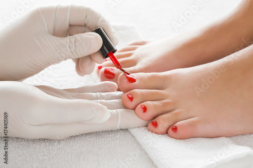 Foto op Canvas Pedicure Hands in gloves cares about a woman's foot nails. Pedicure, manicure beauty salon concept. Nail varnishing in red color.