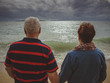 An elderly couple holding hands, looking at the storm at sea. Rear view, back to camera