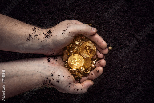 Fotografía  Gold nuggets with a bitcoin in the hands of the miner