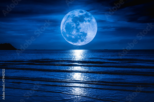 La pose en embrasure Nuit Super moon. Colorful sky with cloud and bright full moon over seascape.