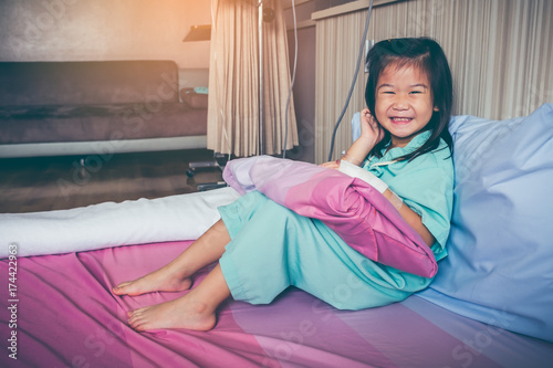 Fotografie, Obraz  Illness asian child admitted in hospital with saline intravenous on hand