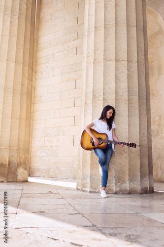 Plakat Kobieta bawić się gitarę przy Antyczną świątynią