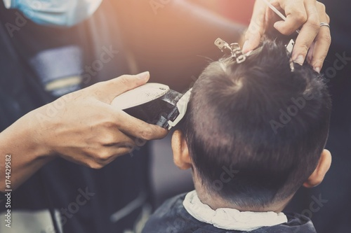 Side view of  little boy getting haircut by hairdresser at the barbershop Wallpaper Mural