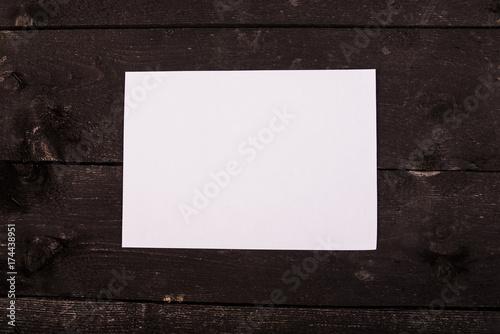 Fototapeta Drewniany stół z białą kartką na środku. Mock up. Mock up na menu, katalog. Starodawny stół. Drewniane tło. obraz