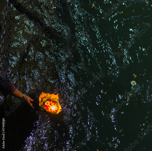 Holy ghats at Haridwar, India, sacred town for Hindu religion. Pilgrims offering floating flowers and burning candles to the Ganges River.