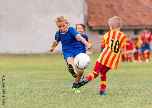 Kids soccer football - little girl is shooting ball at soccer field
