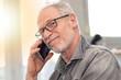 Portrait of smiling mature man talking on phone, light effect