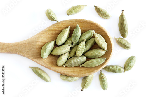 Fototapeta Raw organic green cardamom pods in wooden spoon isolated on white background. Top view obraz