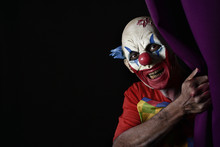 Scary Evil Clown Peering Out From A Stage Curtain
