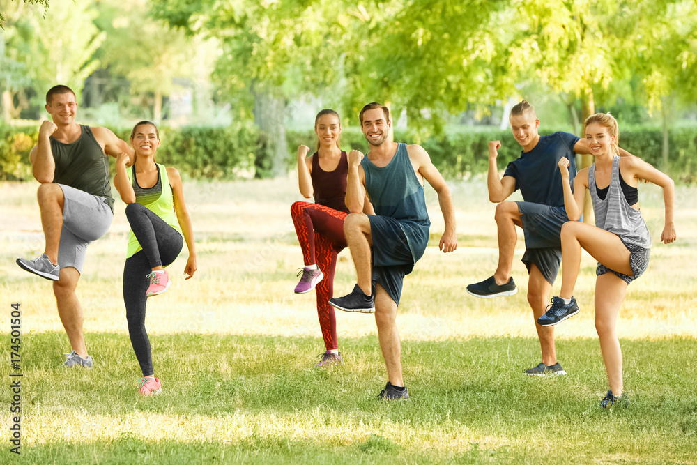 Fototapety, obrazy: Group of young people doing exercise outdoors
