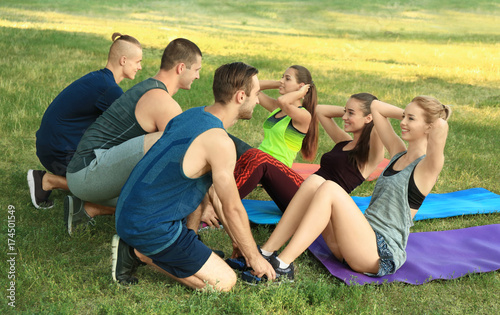 Obraz Young sporty people doing exercise on mats outdoors - fototapety do salonu