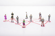Miniature Business People In Conection Scheme Over White Backdrop Or Background.