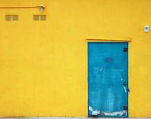 Aqua Blue Industrial Door On A Bright Yellow Building