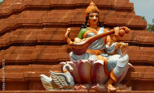 Statue of Hindu Goddess Saraswati play music on veena, with hansa ,her mount,in a  temple
