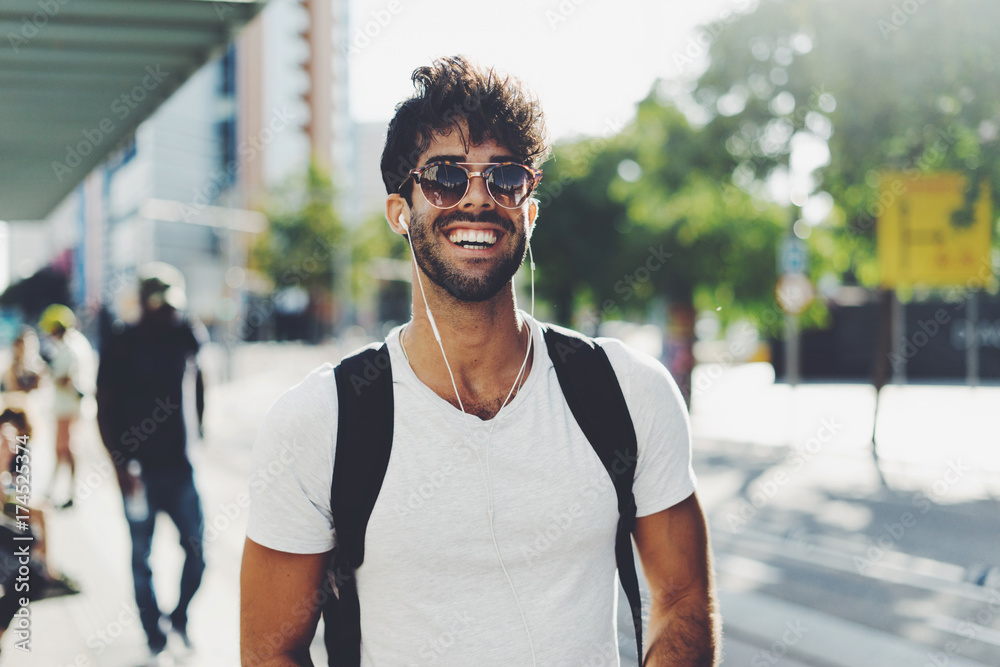 Fototapety, obrazy: Young travel blogger is ready for a new weekend trip. Bearded backpacker is standing on a blurred station background. Student is relaxing on a weekend. Hipster guy wearing sunglasses smiling at camera