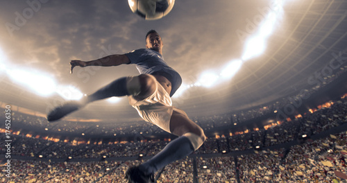 Fotografiet  Soccer player kicks the ball on the soccer stadium
