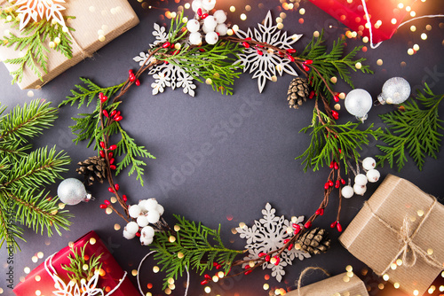 Frame with christmas wreath, gift boxes, branches and snowflakes on ...