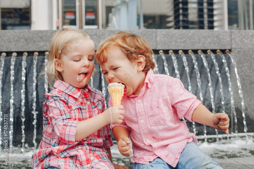 Fotografie, Obraz  Group portrait of two white Caucasian cute adorable funny children toddlers sitting together sharing ice-cream food