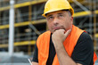 Pensive construction worker with fingers under his chin at work con construction site