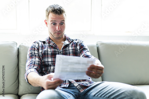 Valokuva  Shocked man holding some documents on sofa livingroom