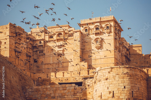 Papiers peints Fortification Birds flying over the towers of historical Jaisalmer fort with monumental stone walls in old city of Rajasthan, India