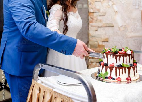 Zdjęcie XXL Panna młoda i pan młody krojenia tortu weselnego z jagodami, owocami i czekoladą. Nowożeńcy cięcia biały wielopoziomowy tort weselny ze świeżych malin, truskawek, jeżyny, winogron i liści mięty
