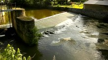 Old Water Of Small River Flow Over Small Stony Weir. Small Water Flowers