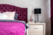 Matrimonial double bed in elegant and comfortable modern bedroom with nightstand lamp closeup. Interior design details