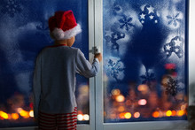 Boy Before Christmas Near Window With Snowflakes