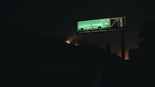 Highway Sign With Wildfire In Background