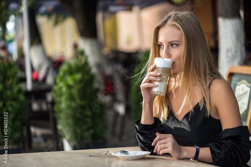 Plakat blondynka pije kawę w kawiarni