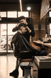 Young barber giving client a classic haircut in vintage barber shop