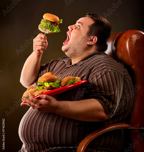 Diet failure of fat man eating fast food hamberger Happy overweight