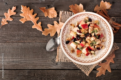 Foto op Canvas Herfst Autumn oatmeal with apples, cranberries, seed and nuts, top view on wood with fall leaves