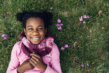 Smiling Black Girl On Grass With Crocus Flowers